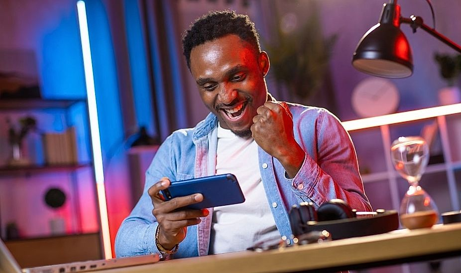 overjoyed african man reading playing on smartphone